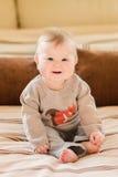 Gelukkige kinderjaren Lachend weinig kind met blond haar en blauwe ogen die gebreide sweaterzitting op bank en wat betreft haar b stock foto