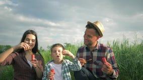 Gelukkige kinderjaren op aard, spelen de jonge ouders met zoon in plaidoverhemden met zeepbels in langzame motiezitting bij gebie stock video