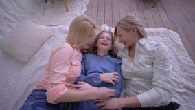 Gelukkige kinderjaren, vallen de leuke meisjes met mamma op bed en hebben thuis samen pret stock footage
