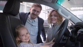 Gelukkige kinderjaren, zoet jong geitjemeisje achter wiel van auto samen met moeder en vader terwijl het kopen van familiemachine stock videobeelden