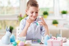 Gelukkige kindjongen die pret hebben tijdens het schilderen eieren voor Pasen in de lente stock afbeelding