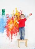 Gelukkige kindjongen het schilderen muur met kleuren stock afbeeldingen
