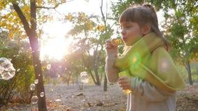 Gelukkige kindspelen met zeepbels in park in zonlicht op aard stock footage