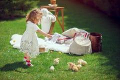 Gelukkige kindspelen op een weide rond Pasen-decoratie royalty-vrije stock afbeeldingen