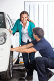 Gelukkige Klant die zich door Mechanisch Changing Tire bevinden Royalty-vrije Stock Foto
