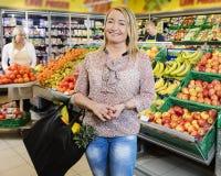 Gelukkige Klant die zich door Verse Vruchten in Kruidenierswinkelwinkel bevinden Stock Foto's