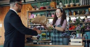 Gelukkige klant het kopen bos van bloemen die met betaalpas in de winkel van de bloemist betalen stock videobeelden