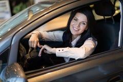 Gelukkige klantenvrouw die een nieuwe auto in dealeshipcentrum kopen royalty-vrije stock foto