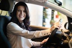 Gelukkige klantenvrouw die een nieuwe auto in dealeshipcentrum kopen stock fotografie