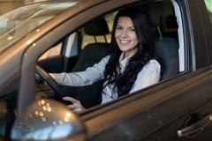 Gelukkige klantenvrouw die een nieuwe auto in dealeshipcentrum kopen stock foto's