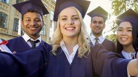 Gelukkige klasgenoten in academische kleding die selfie op graduatiedag nemen, voltooiing stock fotografie
