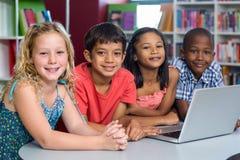 Gelukkige klasgenoten met laptop royalty-vrije stock fotografie