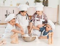 Gelukkige kleine chef-koks die deeg in de keuken voorbereiden Stock Afbeelding