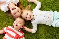 Gelukkige kleine jonge geitjes die op vloer of tapijt liggen Stock Afbeelding