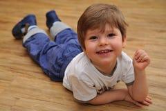 Gelukkige kleine jongen die op houten vloer liggen royalty-vrije stock afbeeldingen