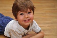 Gelukkige kleine jongen met bruine haren die op de houten grond liggen stock fotografie