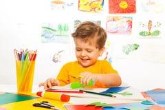 Gelukkige kleine jongensambachten met schaar, document, lijm stock afbeeldingen