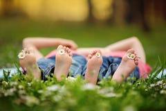 Gelukkige kleine kinderen, die in het gras liggen, blootvoets, madeliefjesaro Stock Afbeeldingen