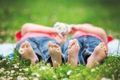 Gelukkige kleine kinderen, die in het gras liggen, blootvoets, madeliefjesaro stock foto