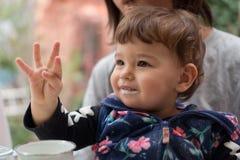 Gelukkige kleine kindzitting in de overlapping van het mamma royalty-vrije stock fotografie