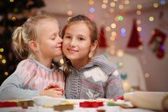 Gelukkige kleine zusters die Kerstmiskoekjes voorbereiden Royalty-vrije Stock Foto's