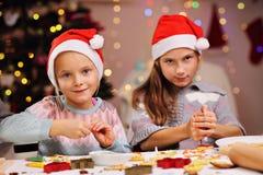 Gelukkige kleine zusters die Kerstmiskoekjes voorbereiden Royalty-vrije Stock Foto