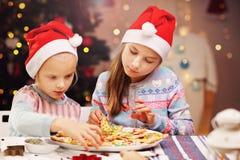 Gelukkige kleine zusters die Kerstmiskoekjes voorbereiden Royalty-vrije Stock Afbeelding