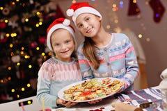 Gelukkige kleine zusters die Kerstmiskoekjes voorbereiden Stock Fotografie