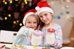 Gelukkige kleine zusters die Kerstmiskoekjes voorbereiden Stock Foto