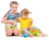 gelukkige kleine zusters met haar konijn stock foto's