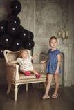 Gelukkige kleine zusters met zwarte ballons Stock Foto's