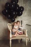 Gelukkige kleine zusters met zwarte ballons Stock Foto