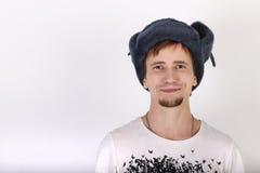 Gelukkige knappe jonge mens in grijs GLB met earflapsglimlachen stock afbeeldingen