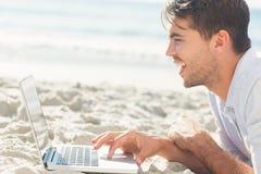 Gelukkige knappe mens op het strand die zijn laptop met behulp van Stock Fotografie