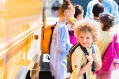 gelukkige krullende schooljongen met zijn klasgenoten status stock fotografie
