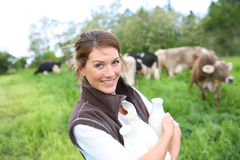 Gelukkige kweker die verse melk, koeien in de rug houden Stock Afbeeldingen