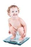 Gelukkige lachende baby die op haar gewicht op een schaal letten Royalty-vrije Stock Foto's