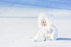Gelukkige lachende baby in sneeuw op zonnige de winterdag Royalty-vrije Stock Afbeelding