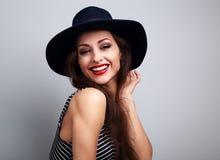 Gelukkige lachende jonge vrouw die in zwarte hoed op blauwe backgrou kijken stock fotografie