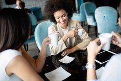 Gelukkige lachende meisjes die koffie hebben en nieuw creatief project in koffie bespreken royalty-vrije stock afbeeldingen