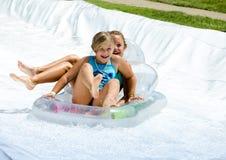 Gelukkige lachende meisjes op een waterdia Stock Fotografie