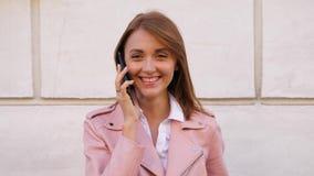 Gelukkige lachende op mobiele telefoon spreken en vrouw die in camera kijken stock videobeelden