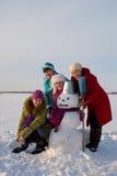 Gelukkige ladiesl vier met sneeuwman royalty-vrije stock afbeelding
