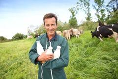 Gelukkige landbouwer met flessen vers verzamelde koemelk Royalty-vrije Stock Foto