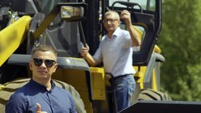 Gelukkige landbouwer met tractorsleutels die zich bij tractor` s treden bevinden stock videobeelden