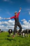 Gelukkige landbouwer op gebied met koeien Royalty-vrije Stock Foto's