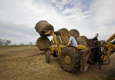 Gelukkige Landbouwer op Tractor met de Ronde Balen van het Hooi stock foto's