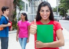 Gelukkige Latijnse vrouwelijke student in rood overhemd die duim tonen stock foto's