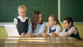 Gelukkige leraar die laptop met leerlingen in het klaslokaal met behulp van stock video