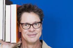 Gelukkige leraar met boeken in hand tonende mensen stock foto's